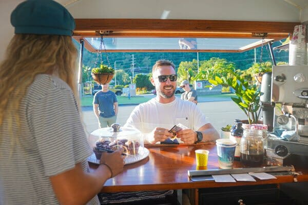 man ordering coffee through window,  Mr Bean coffee caravan, Cannonvale, Whitsunday region