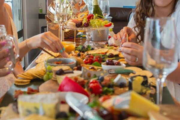 large food grazing platter spread out with girls eating from it, peach and pear catering