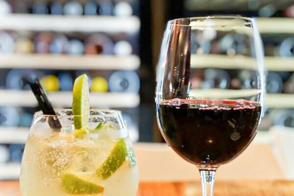 Glass of red wine and lime and soda at The Deck, Main Street Airlie Beach, Whitsunday Region, Queensland
