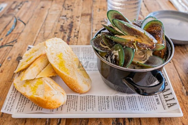 New Zealand Green Lipped Mussels on a table with crispy bread