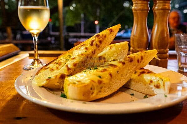 Cheesy Garlic Bread with a glass of white wine in the evening at Banjos, Bar & Bistro, Cannonvale, Whitsundays