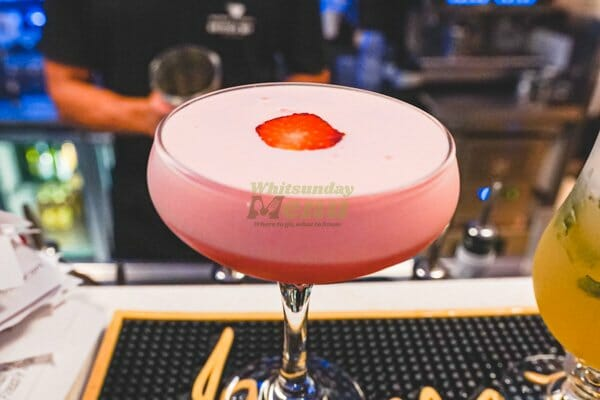 Strawberry Blossom cocktail on the bar at breeze bar, main street Airlie Beach, Whitsunday Region
