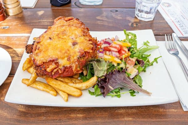 chicken parmigiana, with salad and chips served by KC's Bar & Grill, Main Street Airlie Beach, Whitsunday Region