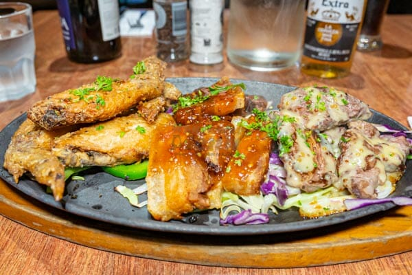 sizzling hot plate with chicken wings and pork belly, Mika, Airlie Beach, Whitsunday Islands, Queensland, Australia