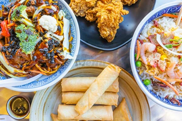 spring rolls, fried chicken, fried rice, noodle dish on a table at Noodle and Rice Airlie Beach, Whitsunday Region, Australia
