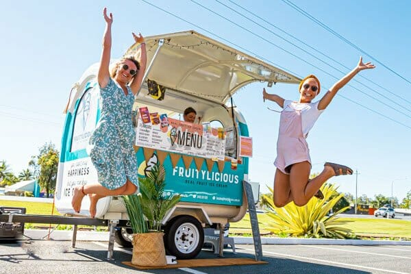 girls jumping in front of ice cream cart, Fruitylicious, Whitsundays, Queensland, Australia