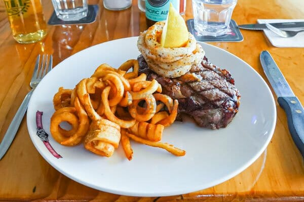 steak and curly fries at hogs breath cafe, airlie beach