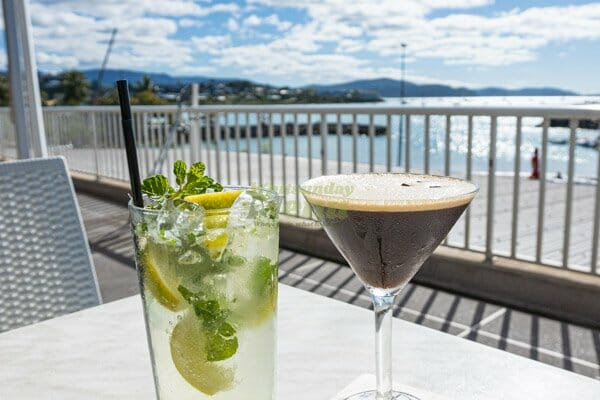 espresso martini and mojito on a table in the sun outside at 20 Degress South Restaurant, Whitsunday Sailing Club, Airlie Beach