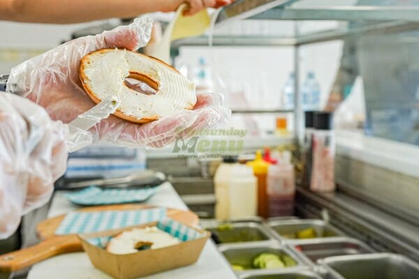 bagel being smeared with cream cheese behind counter at Wisdom Cafe, Whitsundays